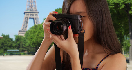Close up of Asian millennial photographer taking photos by the Eiffel Tower