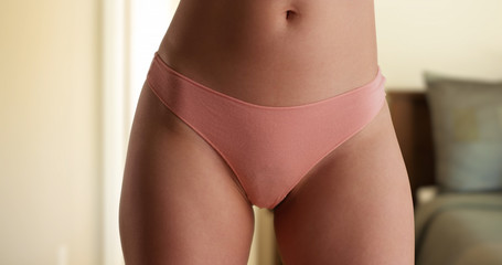 Close up of millennial woman wearing pink underwear in house bedroom