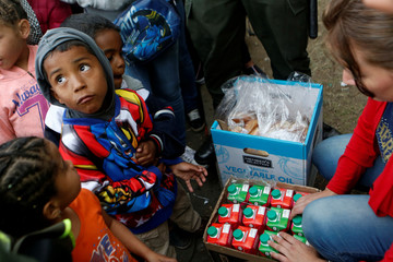 Venezuelan migrant children line up to receive food at a makeshift camp near the transport terminal in Bogota