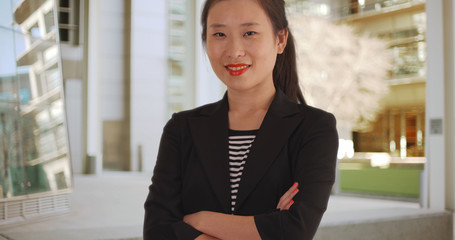 Happy millennial Asian business lady with arms crossed in urban setting