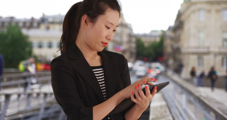 Joyful young Asian business lady using handheld tablet computer in Europe