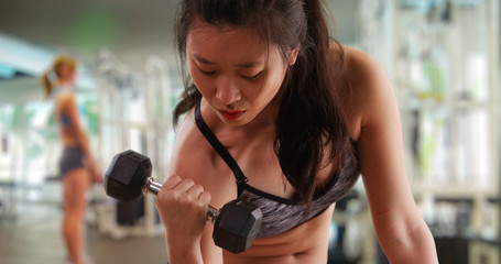 Athletic millennial woman lifting weights indoors at gym