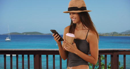 Cute young woman vacationing in the Caribbean texting with smartphone