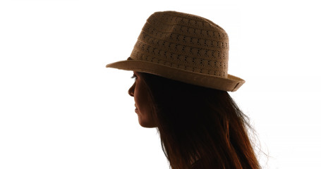 Silhouette of young Caucasian woman in fedora on white background