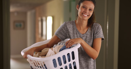 Casual portrait of happy young woman at home holding basket of clean clothes