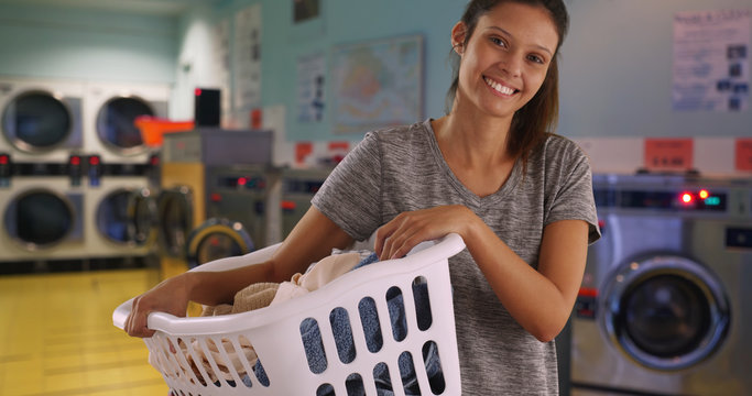 Casual portrait of brunette girl holding basket of clothes in laundry room