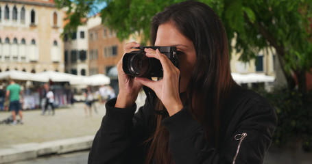 Close up of millennial woman taking photograph of Venice street on vacation