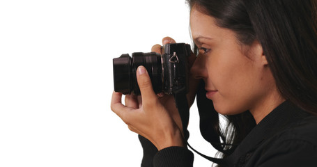 Side view of hipster girl in bomber jacket taking picture with camera in studio