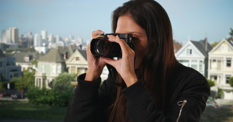 Hipster girl in bomber jacket takes photo in San Francisco neighborhood