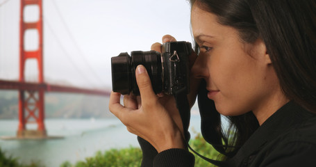 Closeup of tourist woman taking picture with dslr camera near Golden Gate Bridge