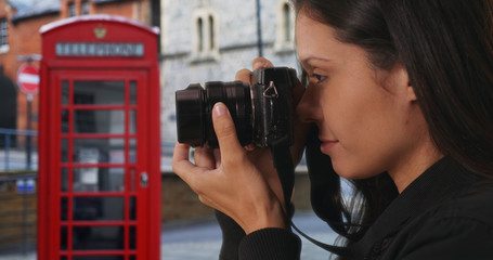Side view of hipster taking photo on England street with red telephone booth