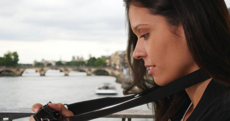 Young travel photographer in Paris taking picture while on bridge over the Seine