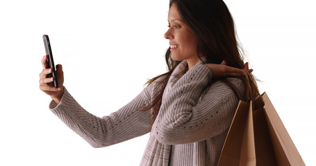Beautiful female takes phone selfie while carrying shopping bags in studio