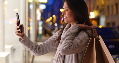 Pretty female holding shopping bags takes selfie while on city street at night