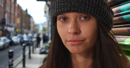 Close up portrait of girl wearing beanie looking at camera on urban city street