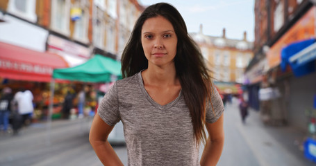 Portrait of Millennial woman looking at camera on street in commercial district