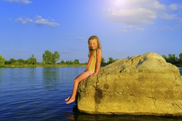 Cute little girl in a bathing suit sitting on a large rock by the lake at sunset. Summer and happy childhood concept. Copy space in bright blue sky