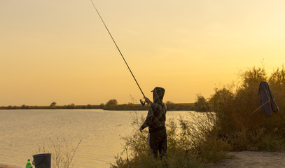 man is fishing at sunset