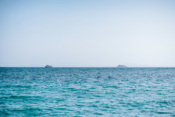 Nautical photograph of the boat sailing in the sea. Island at the horizon of the sea. A clear blue sky and calm sea water.