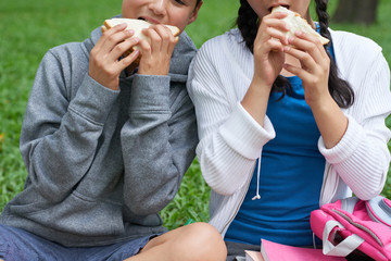 Cropped image of schoolchildren eating tasty sandwiches they took from home