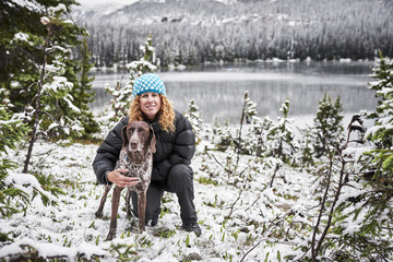 a young woman with curly hair with her hunting dog in front of a mountain lake in the winter