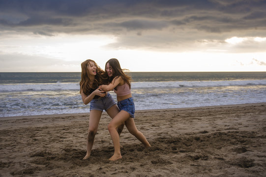 two happy and attractive young Asian Chinese women girlfriends or sisters having fun playing wrestling on sunset beach in beautiful light enjoying summer holidays