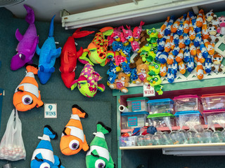 Various live and stuffed fish prizes at a carnival game