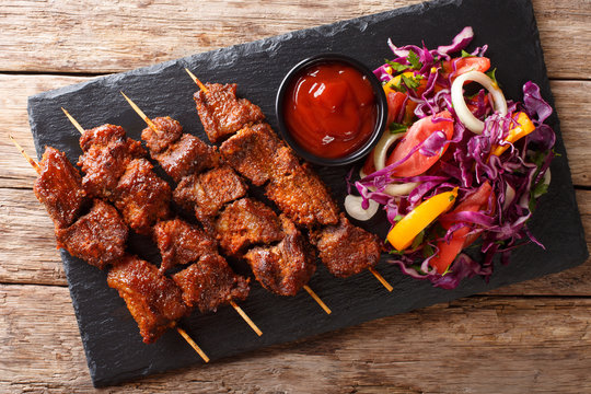 Suya- Roast African spicy skewered beef kebab is served with fresh vegetable salad and ketchup close-up. Horizontal top view