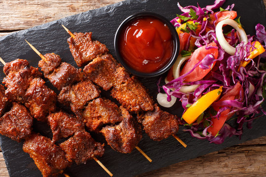 African food: spicy suya kebab on skewers with fresh vegetable salad and ketchup close-up. Horizontal top view
