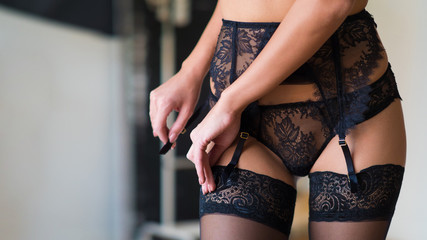 Close up cropped photo of sexy seductive lady, wearing sexy black lingerie with stockings, laces.