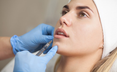 The cosmetologist makes injections of botulinum toxin in the lips of the patient. Cosmetology skin care.