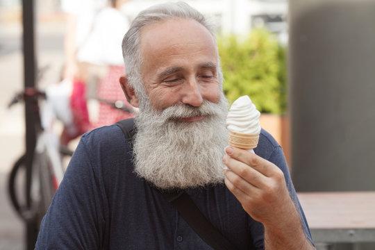 Happy Senior man eating ice cream cone