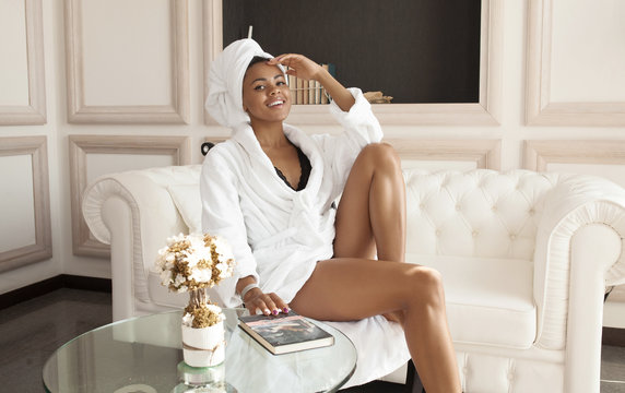 Beautiful glamorous african woman in bathrobe enjoying wellness weekend