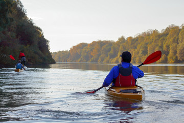 A guy in a yellow kayak rowing in the autumnal river Danube on a calm autumn day