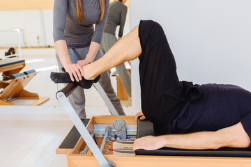 Female instructor with cute braids hairstyle consulting unrecognizable man workout pilates on reformer practice in pilates studio, working out indoor, correcting beginners, сclose up