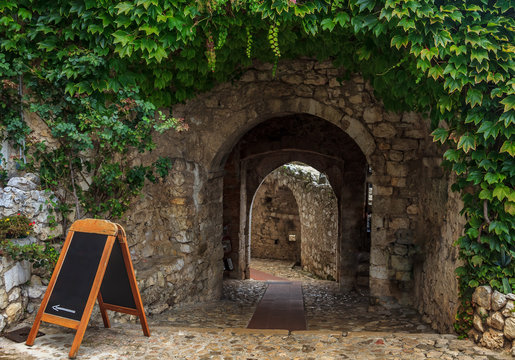 Old ivy covered archway in  the picturesque medieval Eze Village in South of France