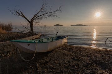 Beautiful view of Trasimeno lake shore (Umbria) at sunset, with some little boats, skeletal tree and sun coming down