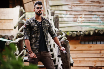 Awesome beautiful tall ararbian beard macho man in glasses and military jacket posed outdoor against wooden stairs.
