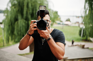 Awesome beautiful tall ararbian beard macho man photographer in glasses and black t-shirt with professional camera at hands.