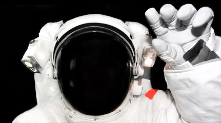 Astronaut in spacesuit raised his hand for a greeting. Spaceman close up in outer space. Elements of this image furnished by NASA