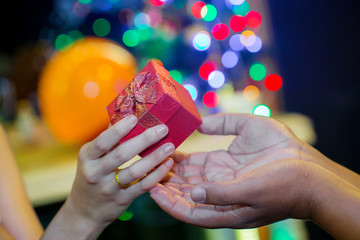 Girl's hand give red gift box to another one person with blurry christmas bokeh lights background. christmas, the giving festival and celebration concept. image for background, symbol and copy space.