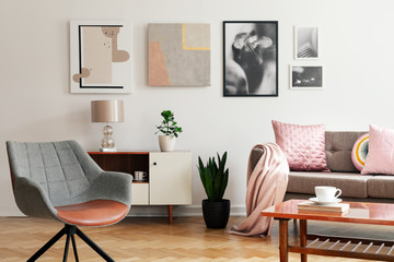 Grey armchair in living room interior with lamp and plant on cabinet next to beige sofa. Real photo