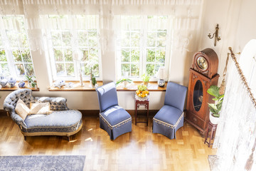 High angle of a silver lounge, blue chairs and wooden clock standing next to windows in luxurious, english style living room interior. Real photo