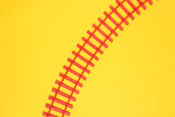 Toy railroad tracks on yellow pastel background. Top View.