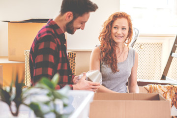 Smiling woman and man packing stuff during relocation to new home