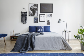 Blanket on bed with blue pillows in white bedroom interior with gallery and lamp on table. Real photo
