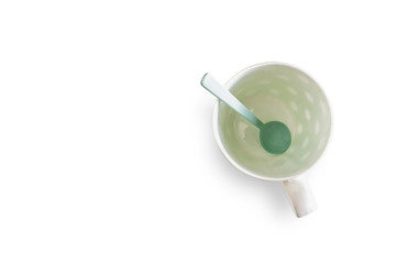 White cup and green spoon separated from the white background with clipping path