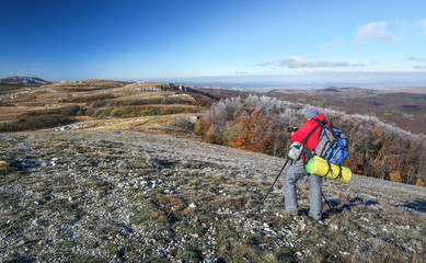 Photographer takes pictures on top of the mountain in autumn. Traveler with backpack enjoying a view from the mountain top