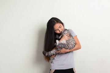 Young happy beautiful Asian woman kissing cute cat