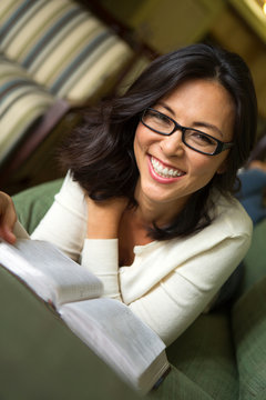 Portrait of an Asian woman smiling and readingl